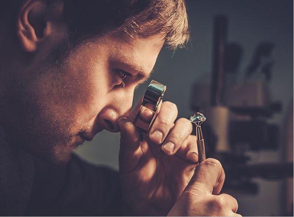 Mężczyzna przyglądający się diamentowi za pomocą lupy