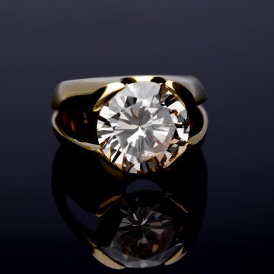 Złoty pierścionek Pierścionek z okrągłym diamentem na czarnym tle